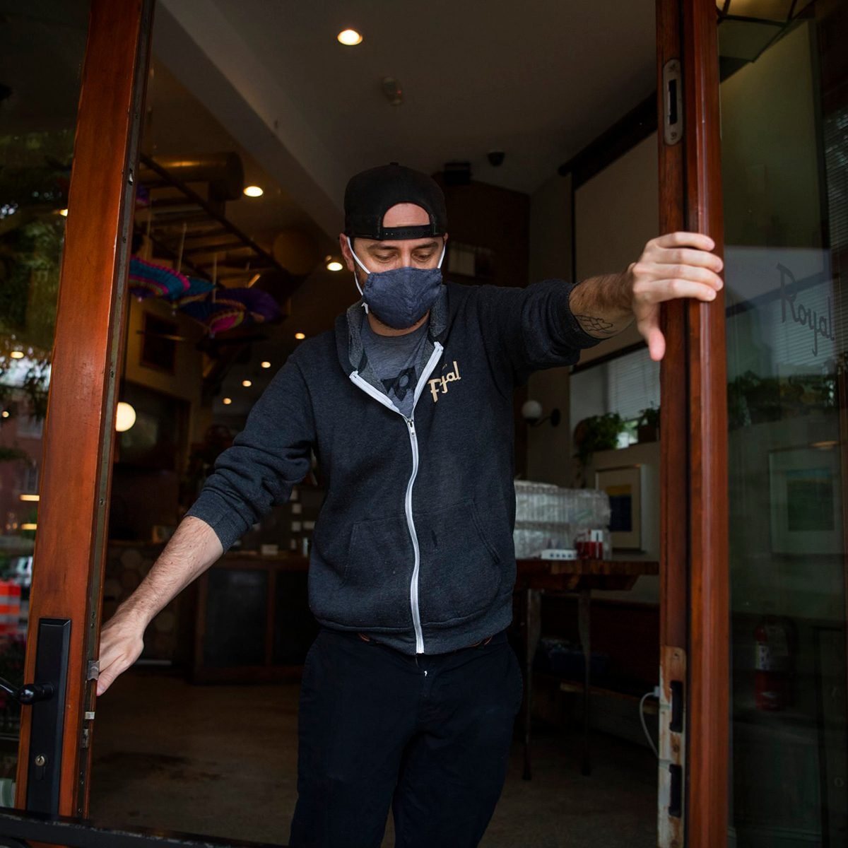 Masked employee at the front door of a restaurant