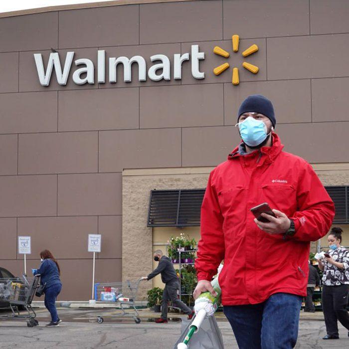 Man wearing a mask walking away from a Walmart