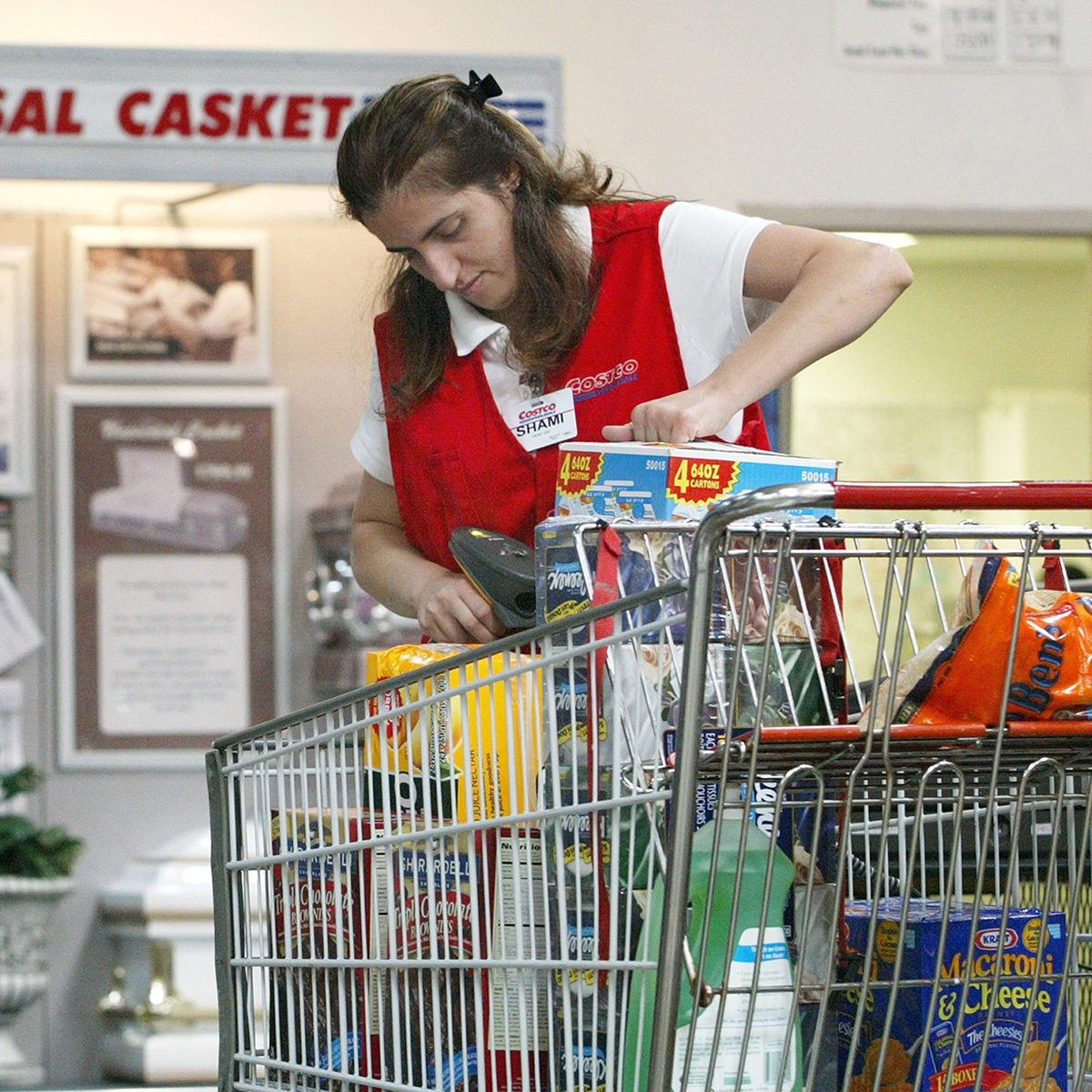 Grocery bagger putting items into a cart