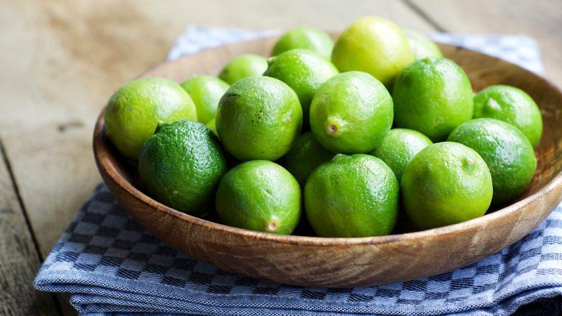Key limes, Citrus aurantiifolia, in a wooden bowl