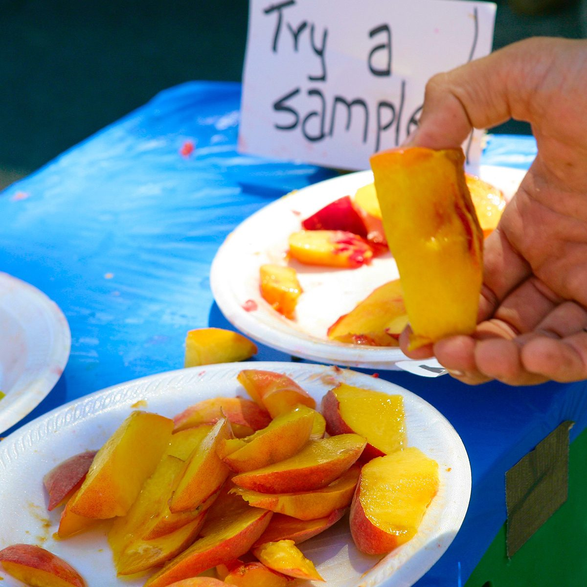 Farmer's market selling fresh, home-grown fruit, cutting samples for shoppers to try.