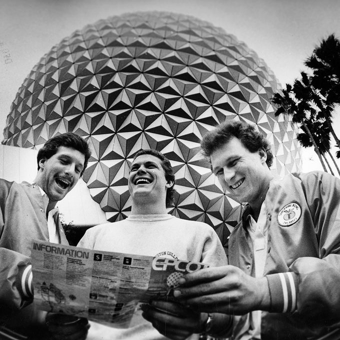 """ORLANDO, FL - DECEMBER 1: Standing in front of the """"Spaceship Earth"""" globe at the EPCOT Center at Walt Disney World, Boston College players, form left, Jim Brown, Scott Nizolek and Brian Krystoforski check a map of the attractions while on tour, December 1982. BC was in town to play Auburn in the Tangerine Bowl. (Photo by John Tlumacki/The Boston Globe via Getty Images)"""