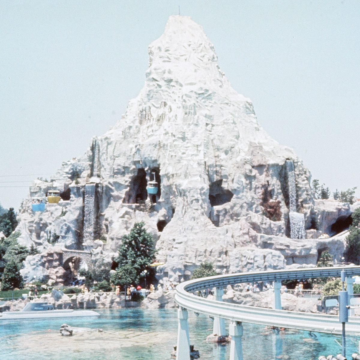 Scenes at the Disneyland theme park in Anaheim, California, United States. Cable cars passinghe Matterhorn mountain attraction and submarine base on the resort. June 1970. (Photo by Monte Fresco/Mirrorpix/Getty Images)