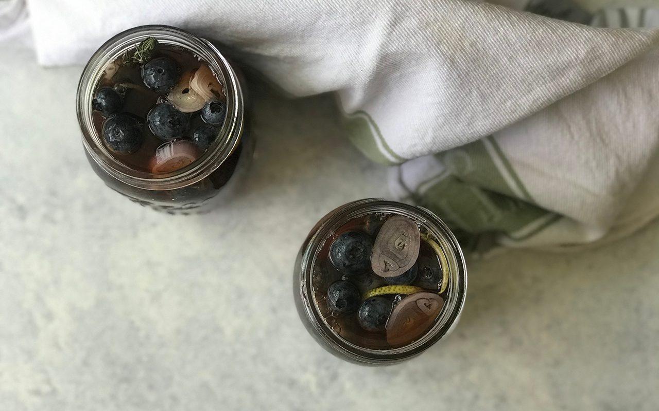 Filled jars of pickled blueberries, overhead