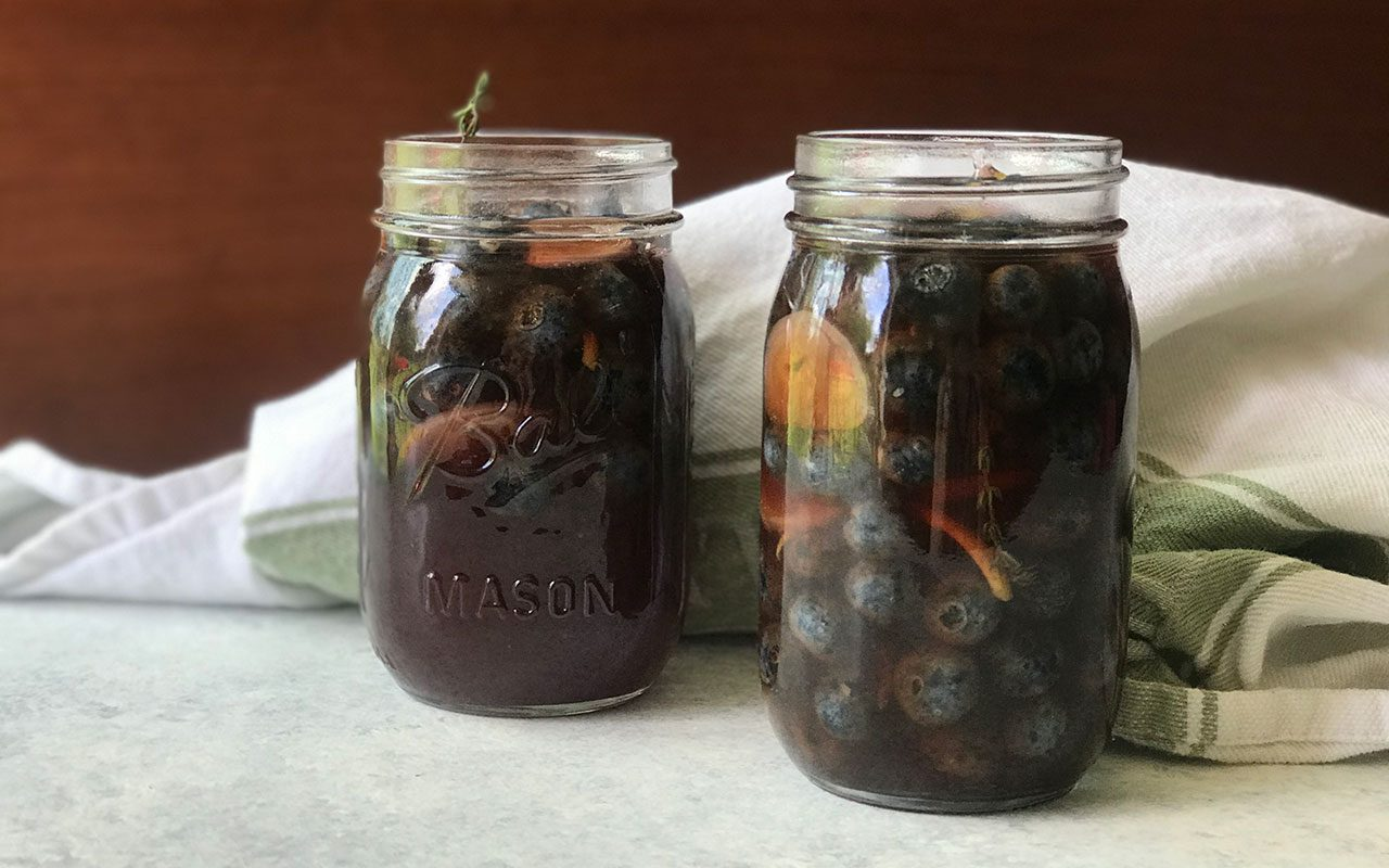 Filled jars of pickled blueberries, head on
