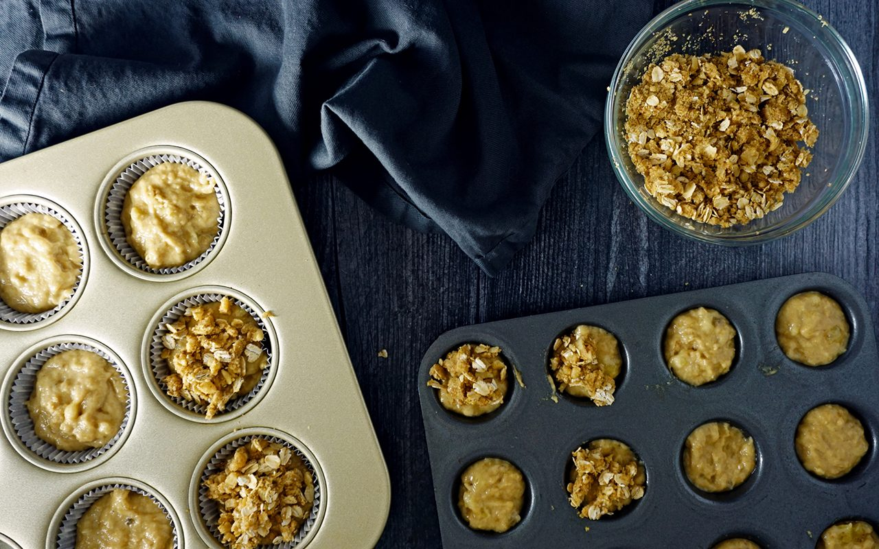 healthy kid-friendly muffin batter in standard and mini muffin tins topped with streusel topping