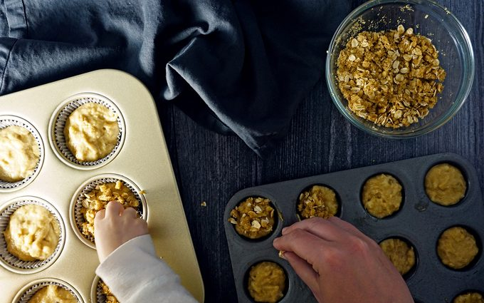 sprinkling streusel topping with a toddler over healthy muffin batter in standard and mini muffin tins