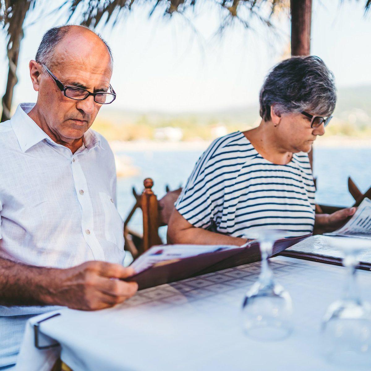 Senior couple reading menus