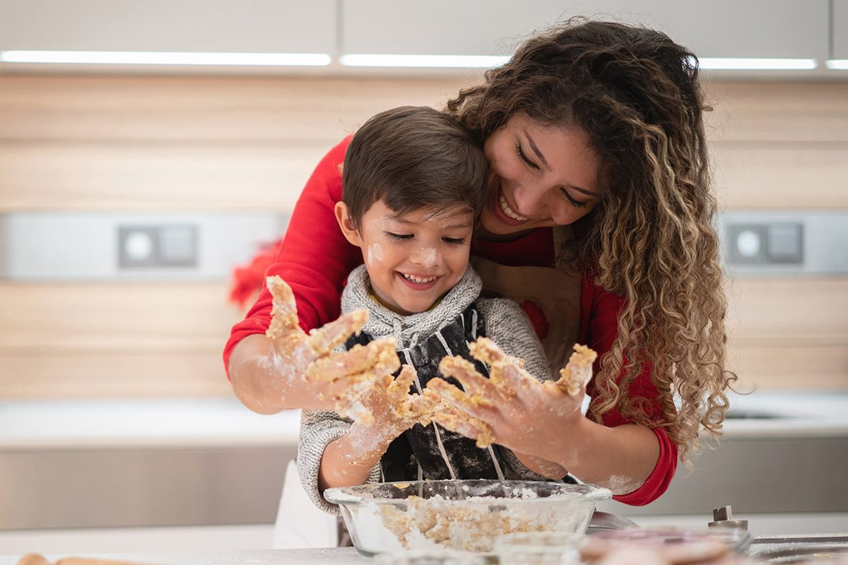 Portrait of a happy mother and son having fun baking cookies and mixing the dough - family lifestyle concepts