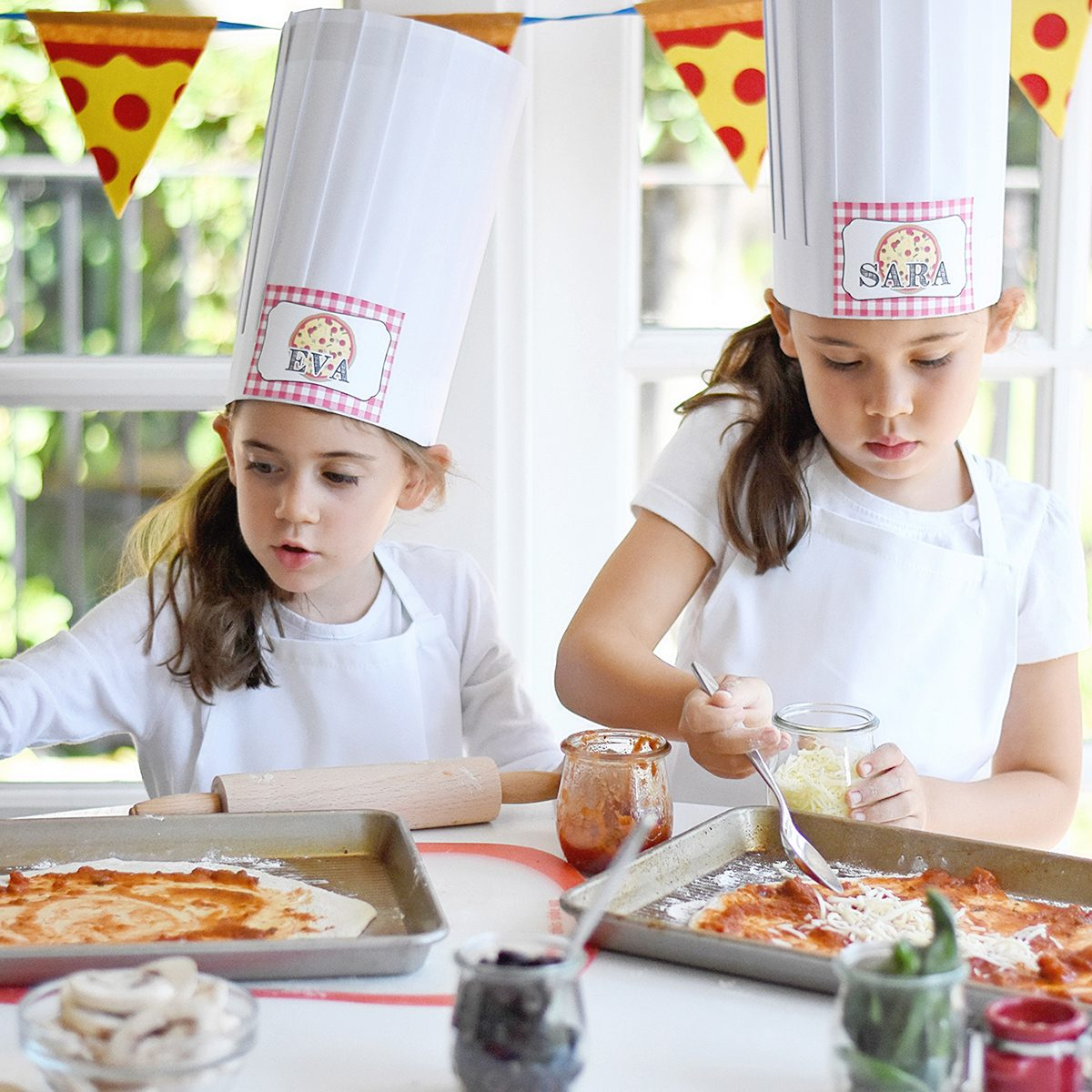 young girls making pizza for Pizza birthday party ideas
