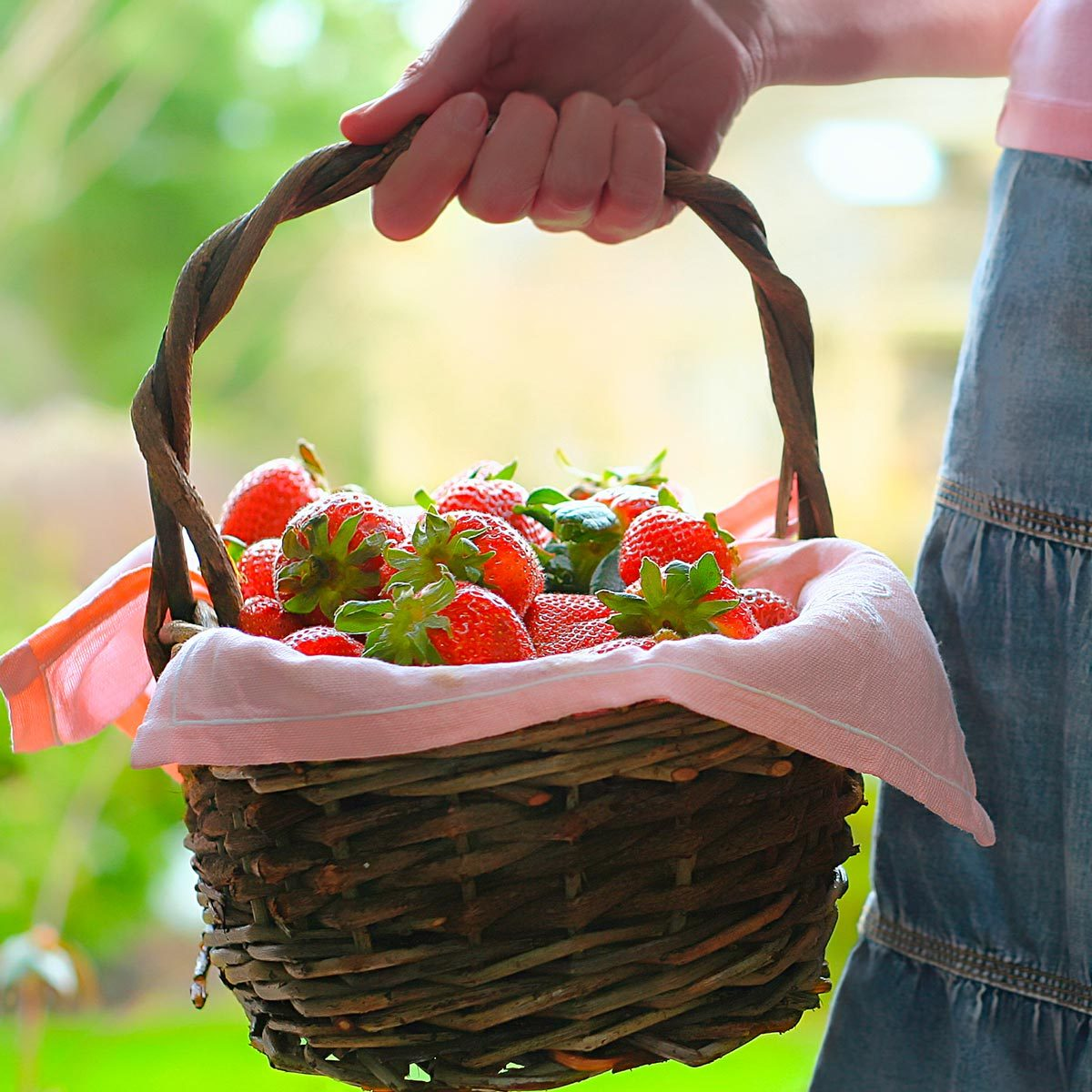 woman in a denim skirt carries a wooden basket full of strawberries