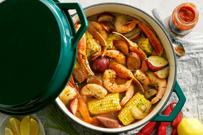 Low Country Boil; overhead camera angle; Wooden farm table surface; Taste of Home Cast Iron Dutch Oven; TOH enameled green 5 qt quart dutch oven with lid; mixed seafood; crab; shrimp; cilantro; sweet corn; potatoes; sausage; newspaper surface; oldbay tin; cocktail sauce; lemons; lemon wedges; Copy Space