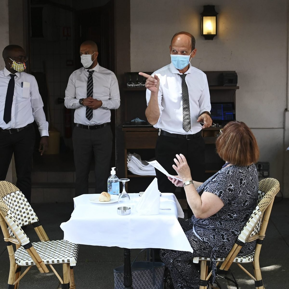 Woman talking to a masked waiter