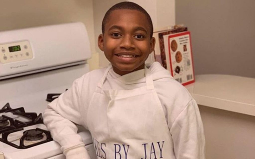 The young baker Jayden leaning against a stove
