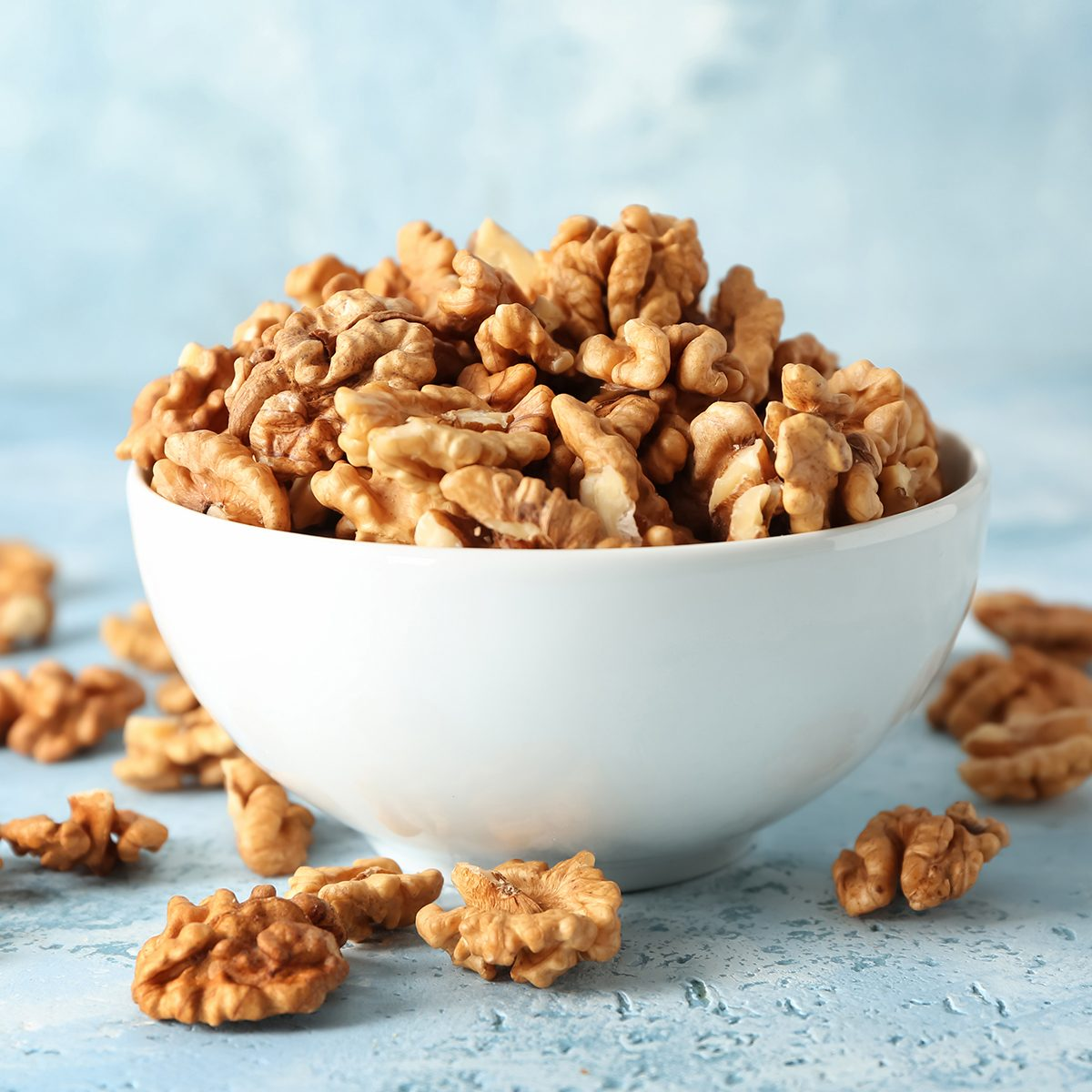 Bowl with tasty walnuts on color table
