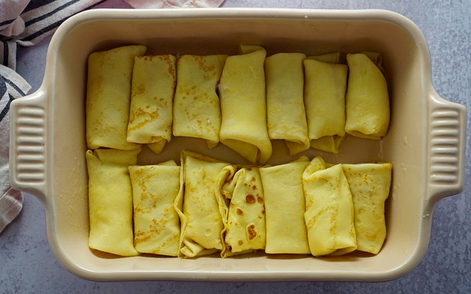a baking dish loaded with a single layer of filled and folded cheese blintzes ready for baking