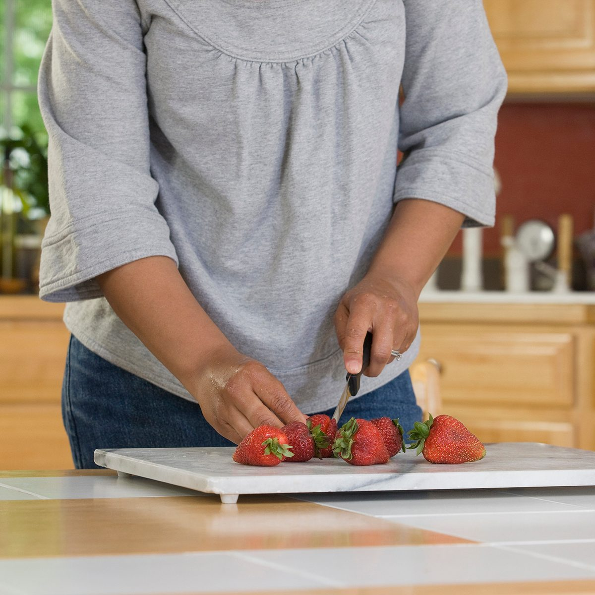 Hispanic woman cutting strawberries in the kitchen