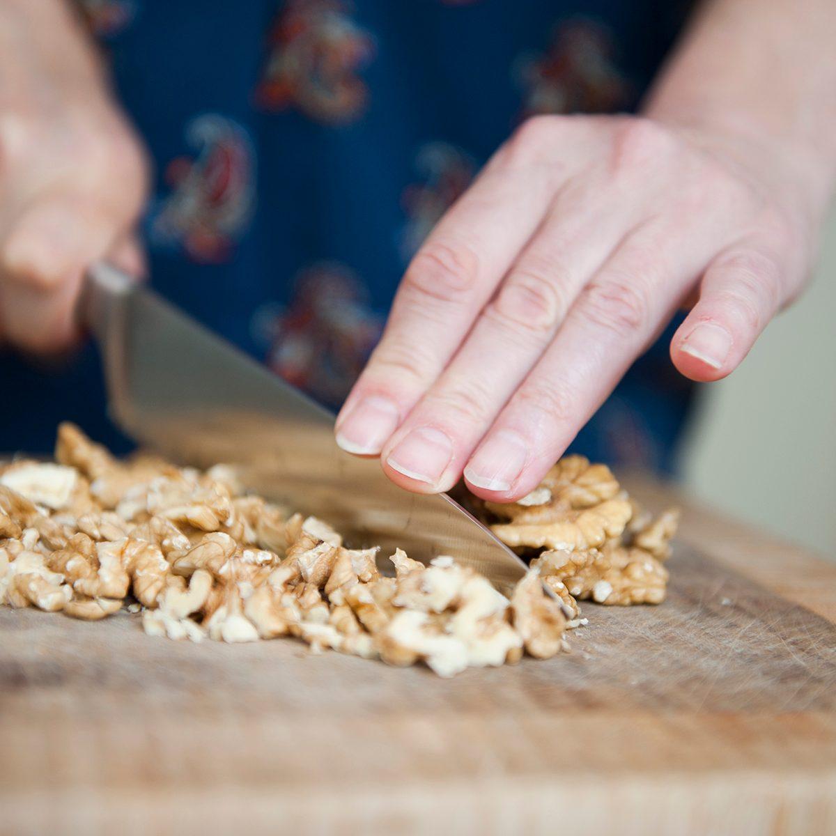 Woman using a big knife to chop walnuts