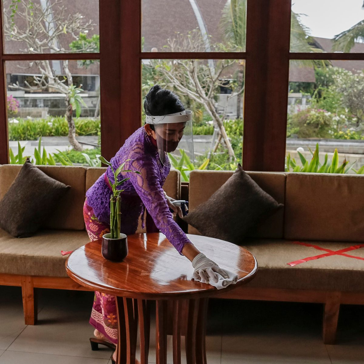 In a restaurant in Bali, an employee is disinfecting the tables