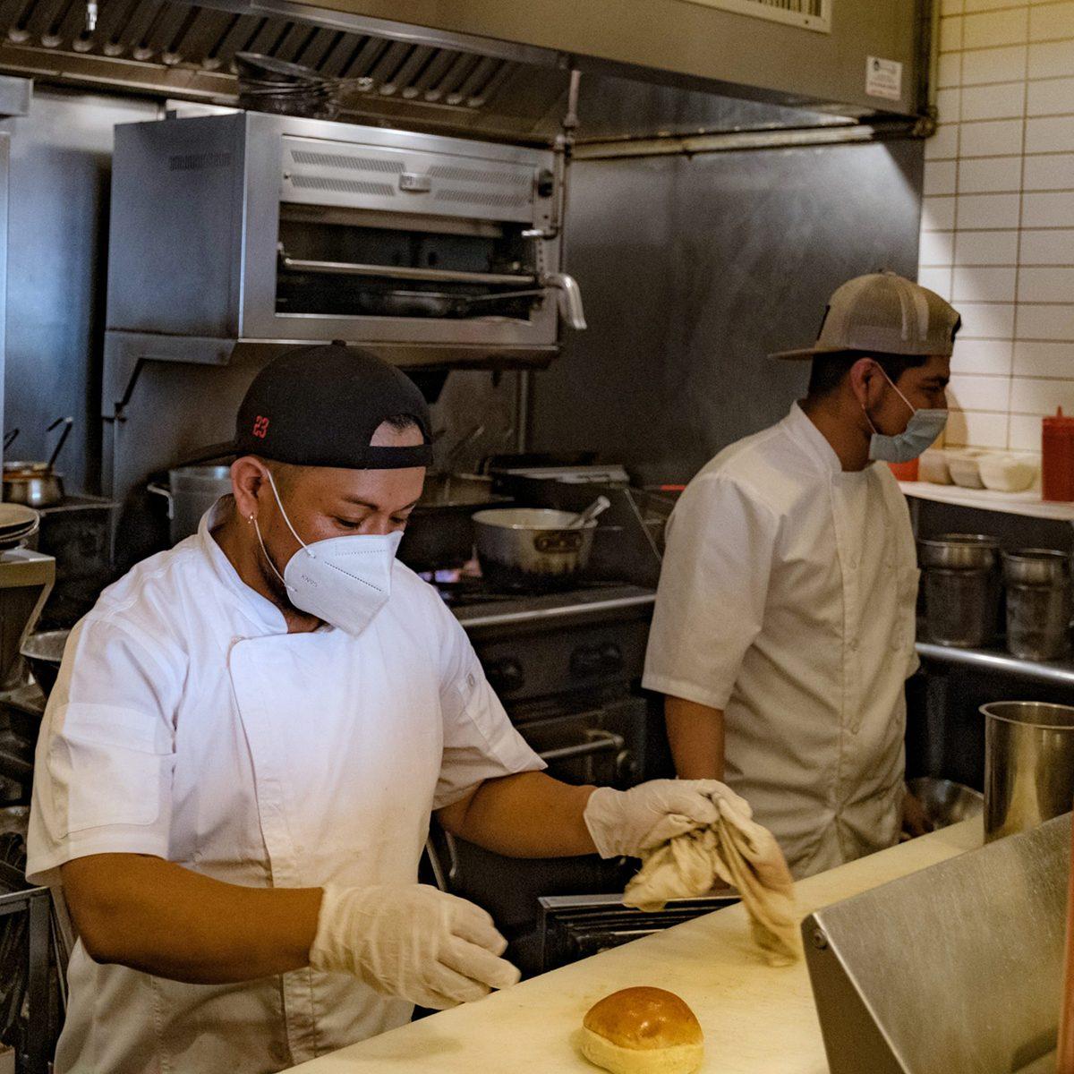 Kitchen staff making food in their masks