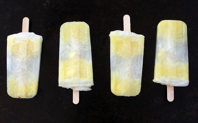 pineapple popsicles on dark background in straight line