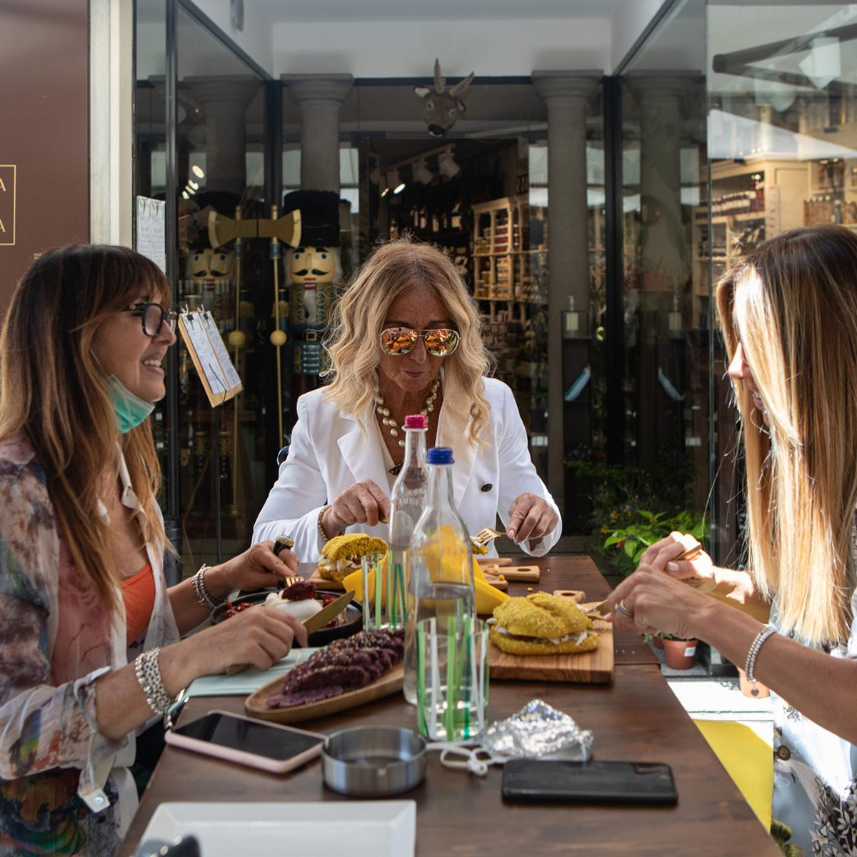 Three women are having dinner at a reopened restaurant