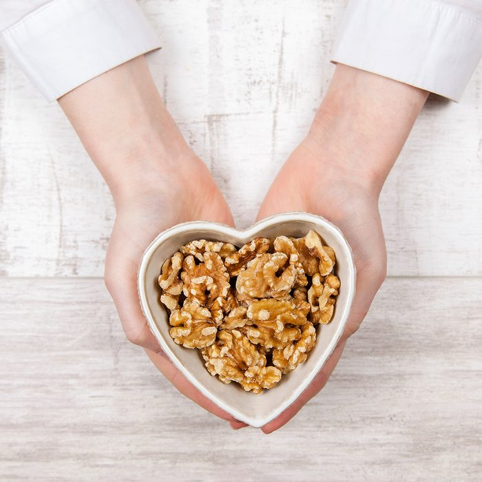 Walnuts in woman hands on white background.