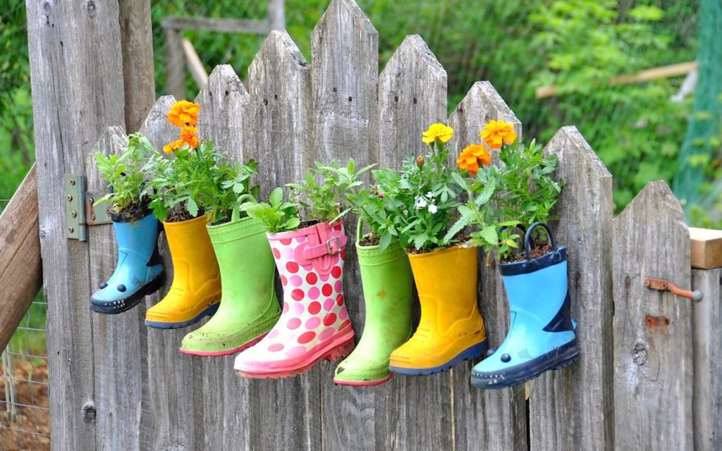 Rain boots with plants in them hanging on a fence
