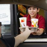 REDWOOD CITY, CA - JULY 29: Josephine Hernandez hands a tray of drinks to a drive thru customer at a McDonald's restaurant July 29, 2003 in Redwood City, California. McDonald's Corporation today reported record second quarter and first half U.S. sales spurred by enthusiasm for its new food offerings and improvement in food taste and service initiatives. Despite the significantly stronger U.S. sales, McDonald?s global profits fell 5 percent as sales in its restaurants in Europe and Asia remained flat.(Photo by Justin Sullivan/Getty Images)