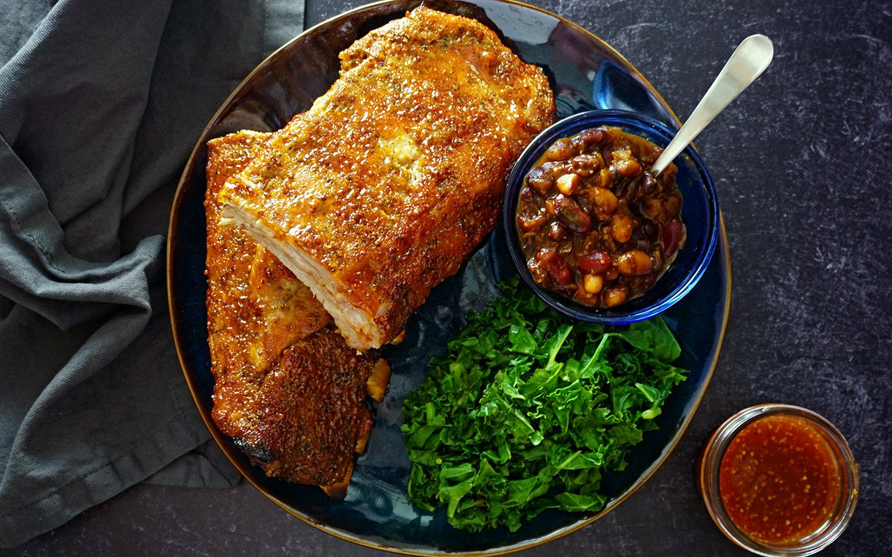 a platter of juicy oven ribs with a side of baked beans and greens overhead