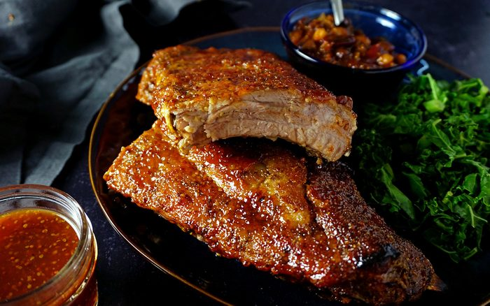 profile view of a platter of juicy oven ribs with a side of baked beans and greens