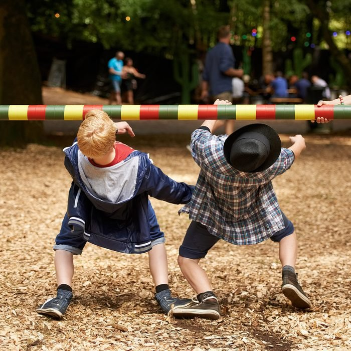 Shot of two kids doing the limbo at an outdoor festival