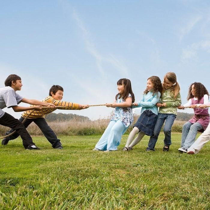 Multi-ethnic children playing tug-of-war