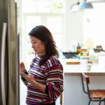 Woman at home in kitchen, using device to order groceries online, e-commerce, inventory, shopping list