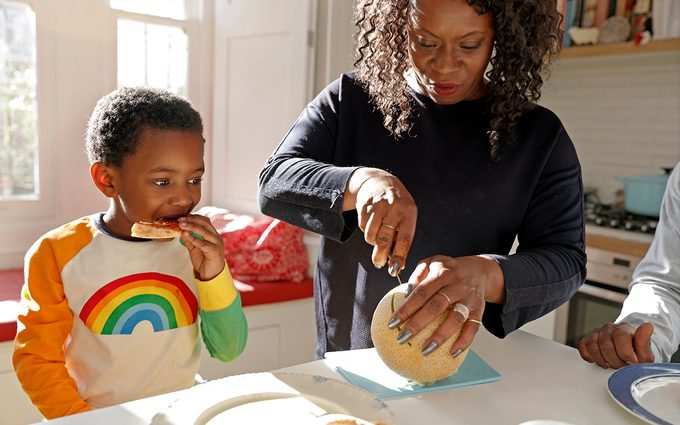 Mother cutting her young son some melon at home in the kitchen