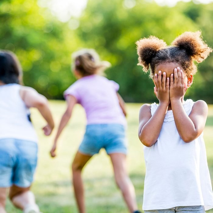 Girls playing hide and seek game in park.