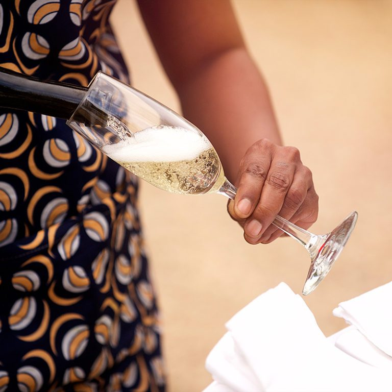 Waiter with African design putting the glass down with sparkling champagne Karoo South Africa
