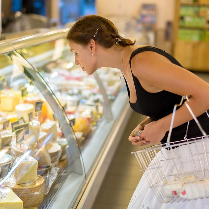 woman buys cheese in the supermarket