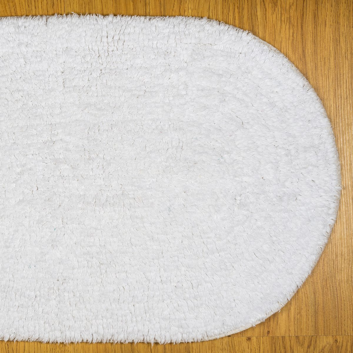 White bathmat over wood floor