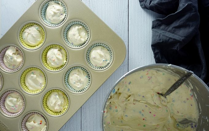 filling cupcake liners with birthday cupcake batter