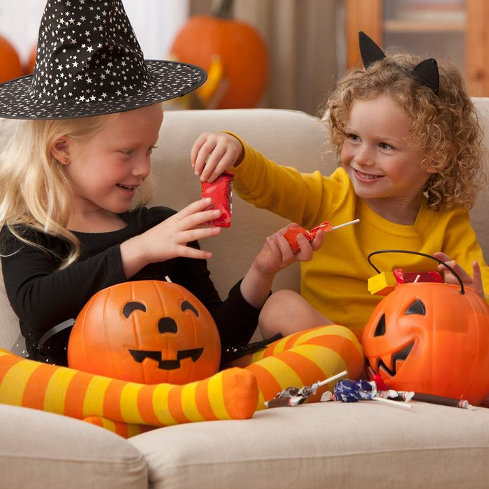 Caucasian girls in Halloween costumes eating candy