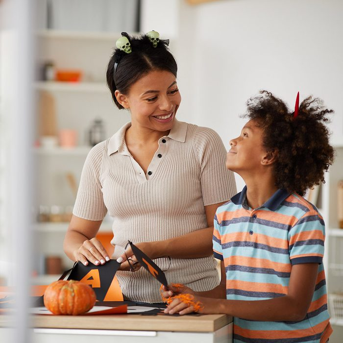 Cheerful young black mother and cute son with Afro hairstyle standing at counter and preparing paper decorations for Halloween with pleasure