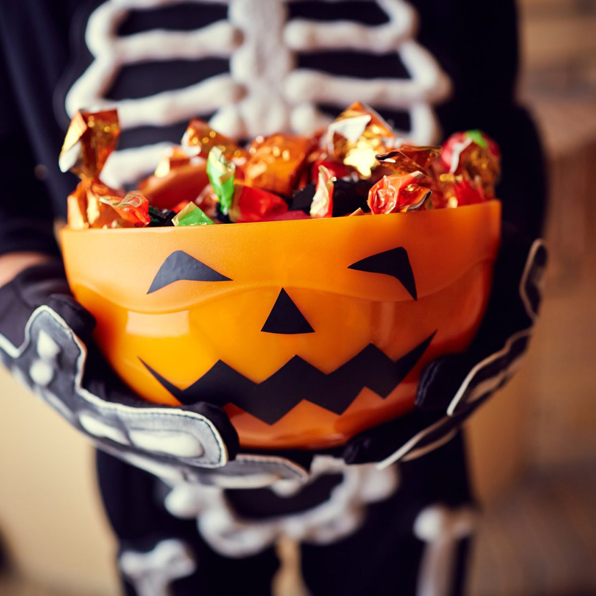 Child in skeleton costume holding a pumpkin candy bowl