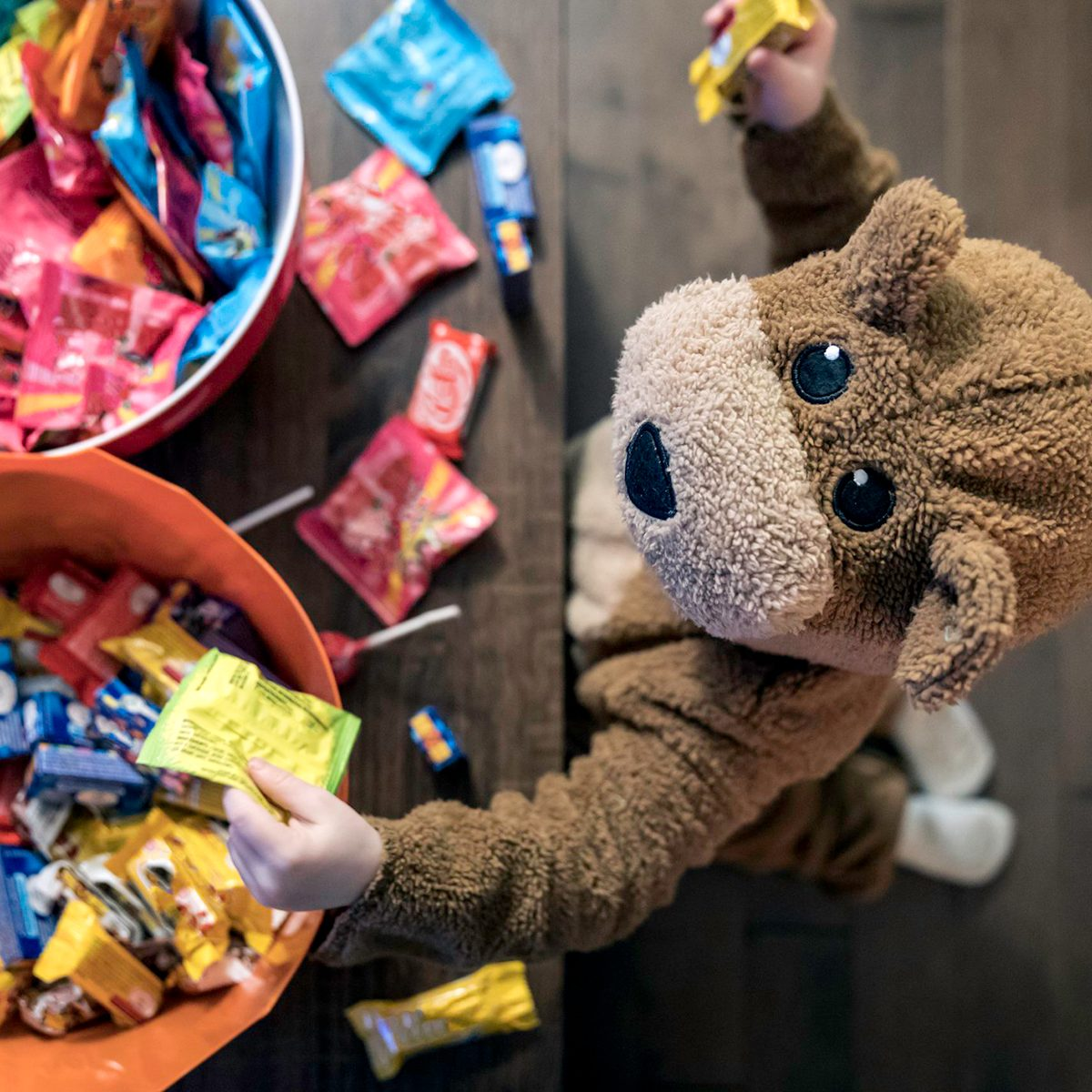 Child in teddy bear costume reaching into candy bowl