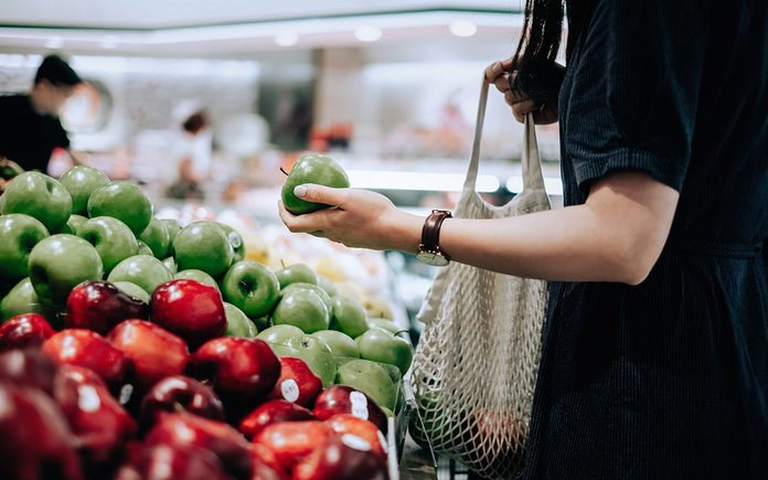 Cropped shot of young Asian woman shopping for fresh organic green apples in supermarket. She is shopping with a cotton mesh eco bag and carries a variety of fruits and vegetables. Zero waste concept