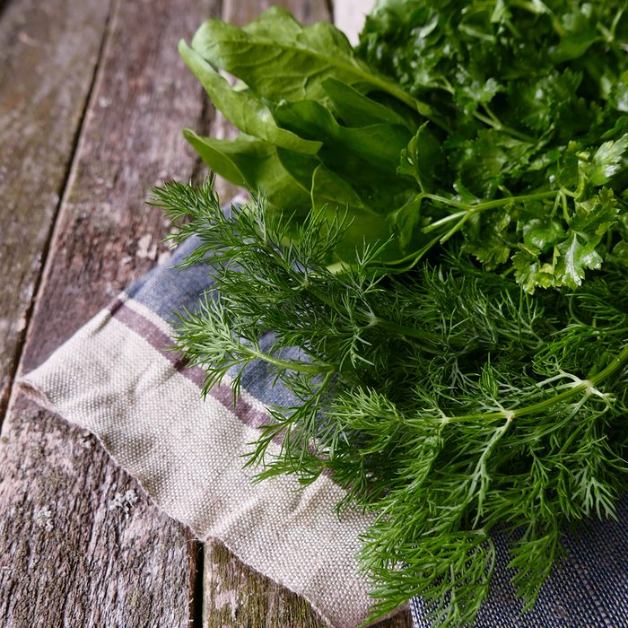 fresh greens on a wooden table linen napkin copyspace