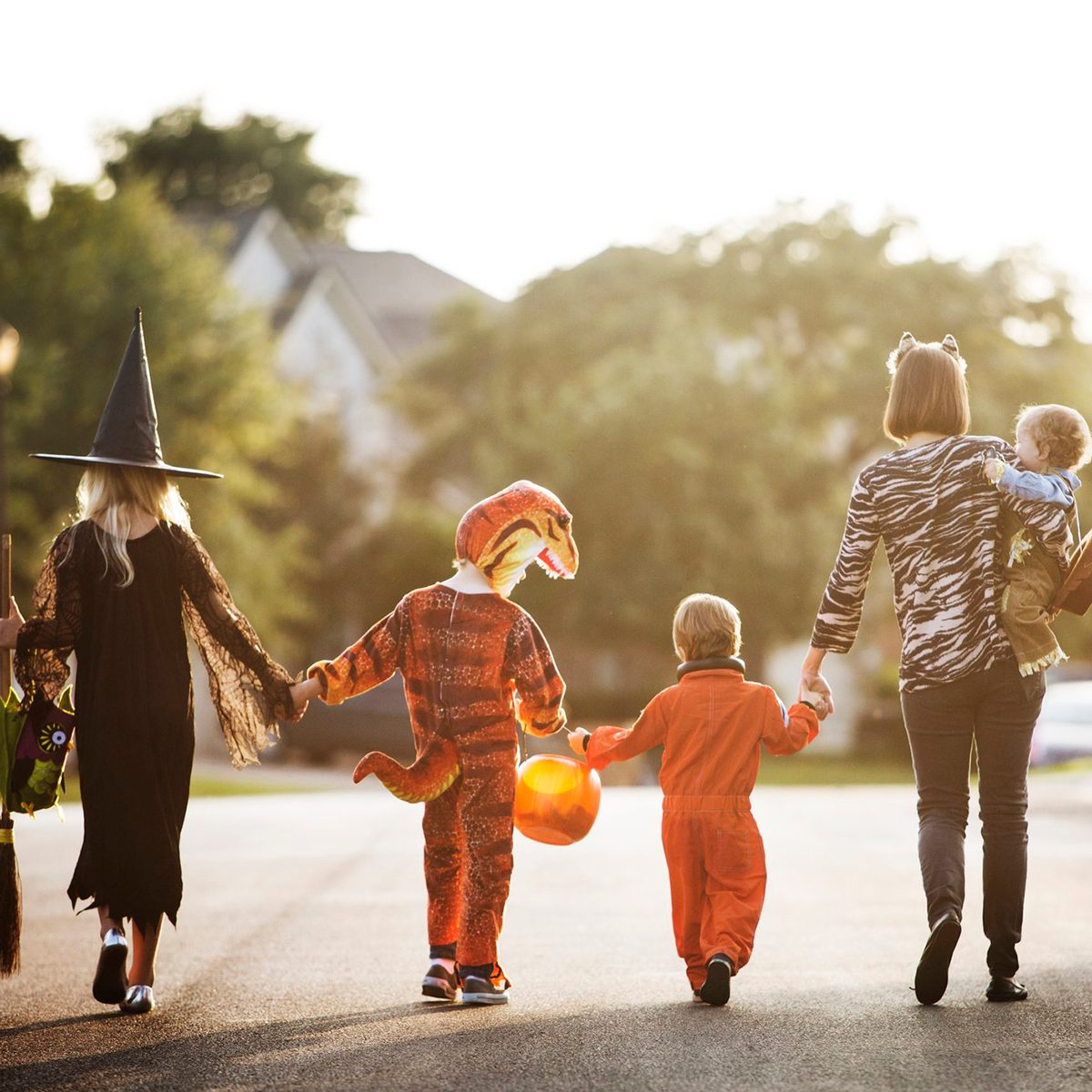 Family in costume holding hands as they walk down the street