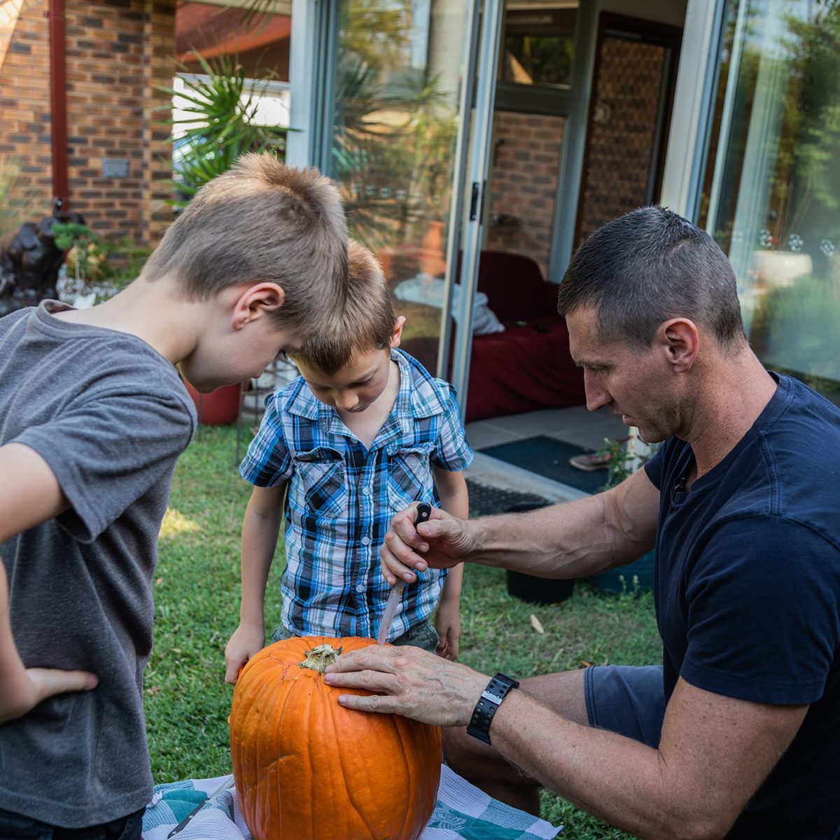 Father and sons carving a pumpkin