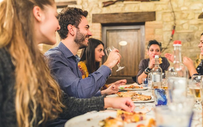 Friends eating pizza together and having fun. Group of friends together at restaurant enjoying proper Italian pizzas. Friendship and Italian food concepts.