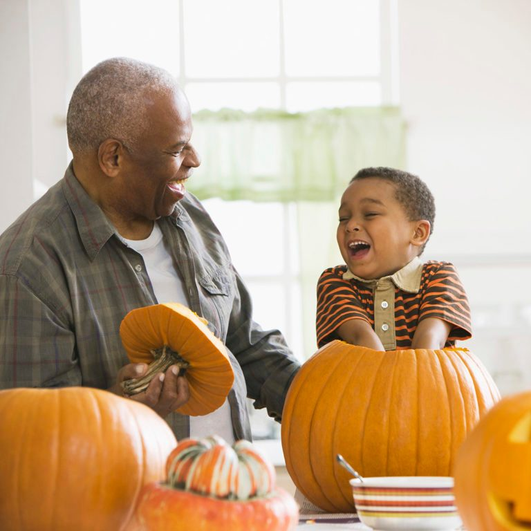 Grandfather and grandson carving a pumpkin